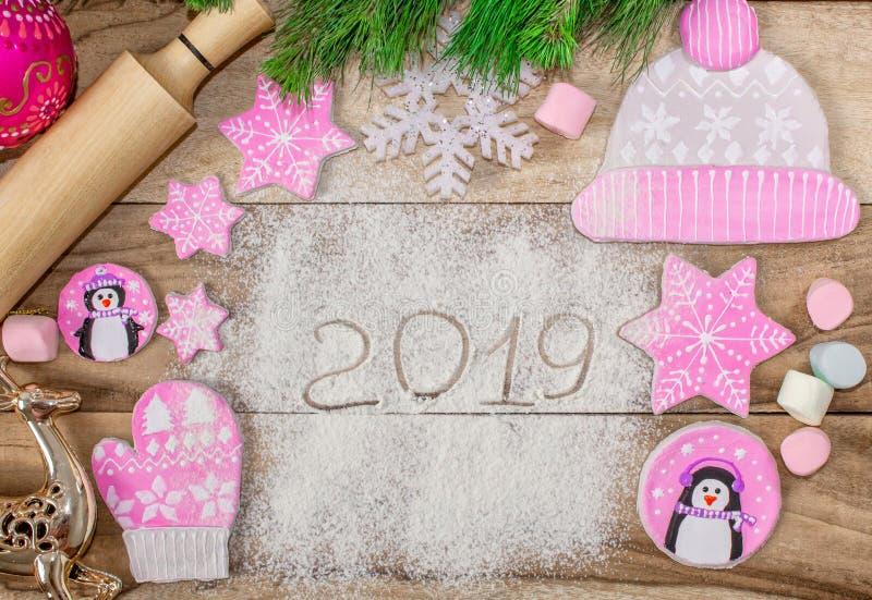 Laga mat för jul Mjöl för att baka, kavel, ljust rödbrun kex i form av pingvin, tumvanten och hattar med stjärnor arkivfoto