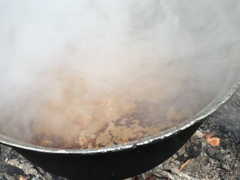 Laga mat gulasch i kittel, yttersida, i en campingplats royaltyfria foton