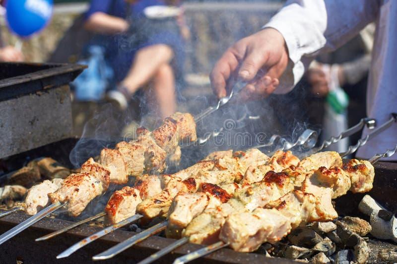Laga mat kebaber på gallret, händer som rymmer en steknål med att ånga kött royaltyfri bild