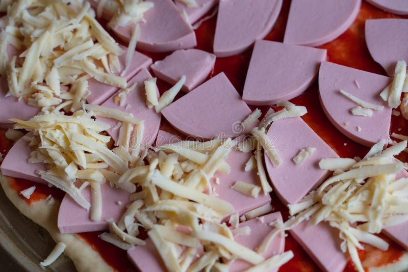 laga mat läcker pizza med skivor av korv- och ostnärbilden royaltyfria bilder