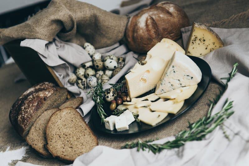 Laga mat läckra smörgåsar för frukostdanandemål med örter, ostar, bröd och annan smaklig mat Beigafärger arkivbild