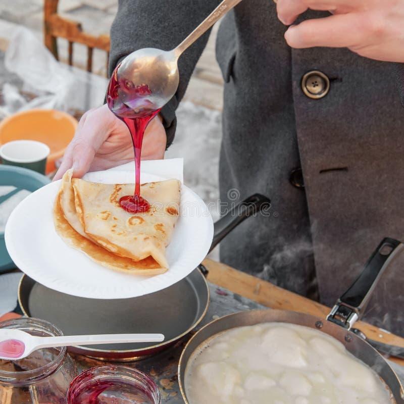 Laga mat pannkakor som är utvändiga i förkylningen Pannkakor stekas i en panna, och ånga kommer ut ur dem avsked som övervintrar  arkivfoton
