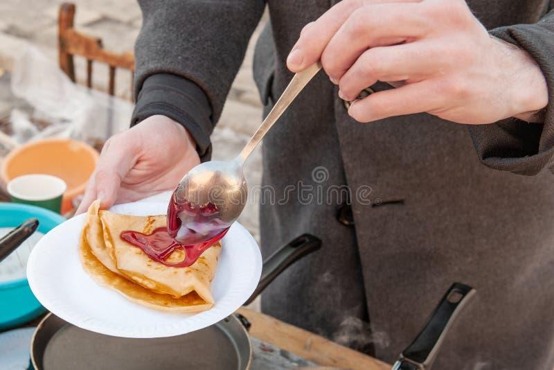 Laga mat pannkakor som är utvändiga i förkylningen Pannkakor stekas i en panna, och ånga kommer ut ur dem avsked som övervintrar  royaltyfri foto