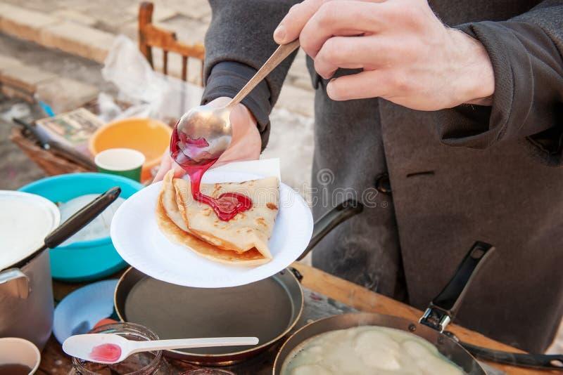 Laga mat pannkakor som är utvändiga i förkylningen Pannkakor stekas i en panna, och ånga kommer ut ur dem avsked som övervintrar  royaltyfri bild