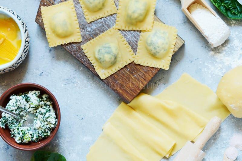 Laga mat Raviolli hemlagad pasta med ricotta och spenat på en blå bakgrund, traditionell italiensk kokkonst arkivbilder