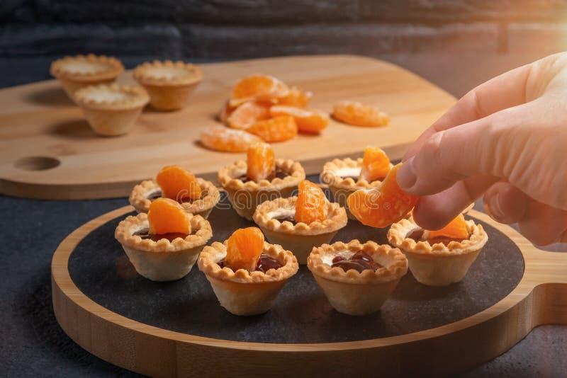 Laga mat söta tartlets med skivor av tangerin och choklad - uppvecklingstangerinskivor fotografering för bildbyråer