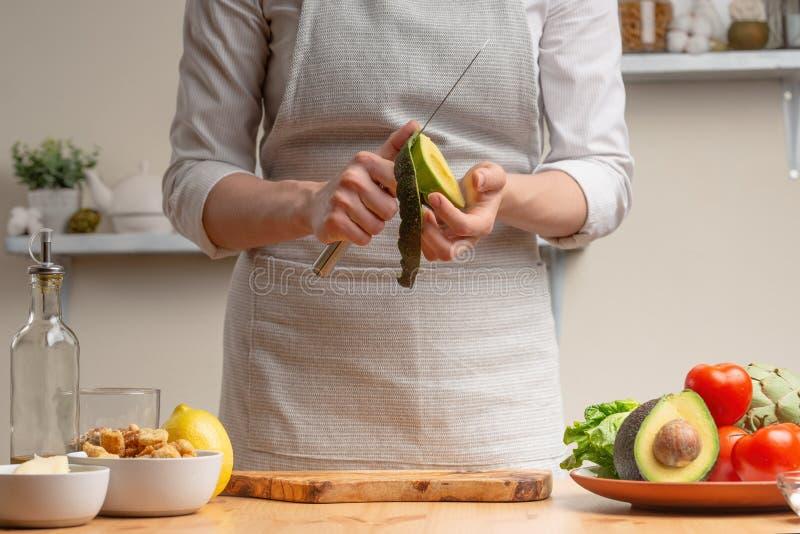 Laga mat smaklig och sund mat Kocken förbereder avokadot för sallad, begreppet av smakligt, och sund mat, bantar, strikt vegetari royaltyfri bild