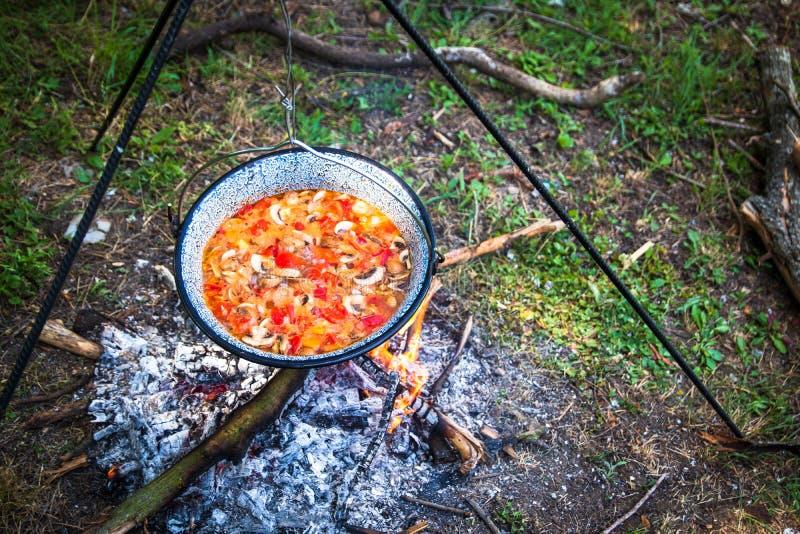 Laga mat som är utomhus- på en brand i en kruka Förbereda gulasch i en natur vid sjön royaltyfria bilder