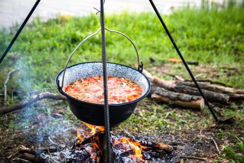 Laga mat som är utomhus- på en brand i en kruka Förbereda gulasch i en natur vid sjön arkivfoto