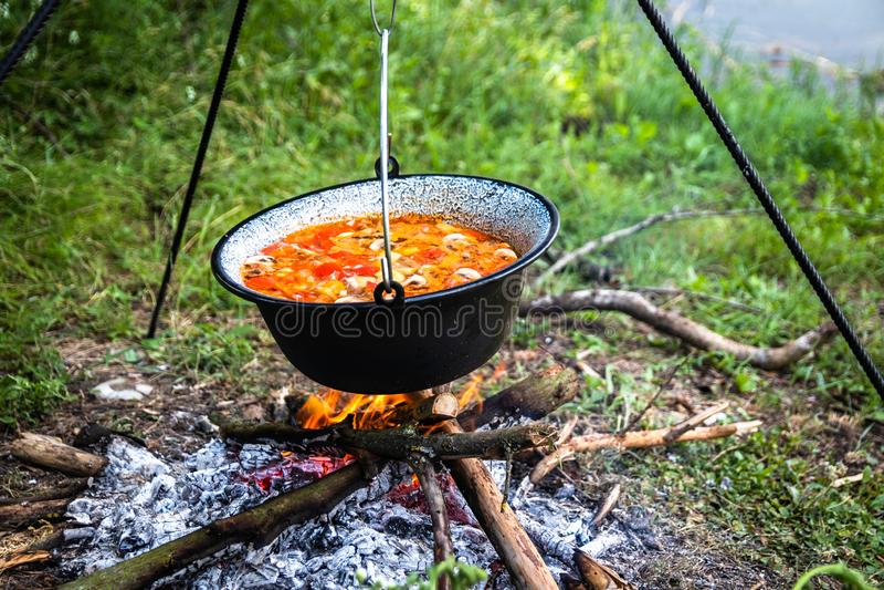 Laga mat som är utomhus- på en brand i en kruka Förbereda gulasch i en natur vid sjön royaltyfri bild
