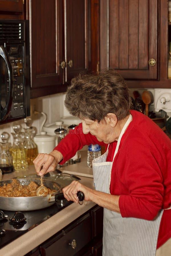 laga mat stekt äldre kvinna för meat royaltyfri foto