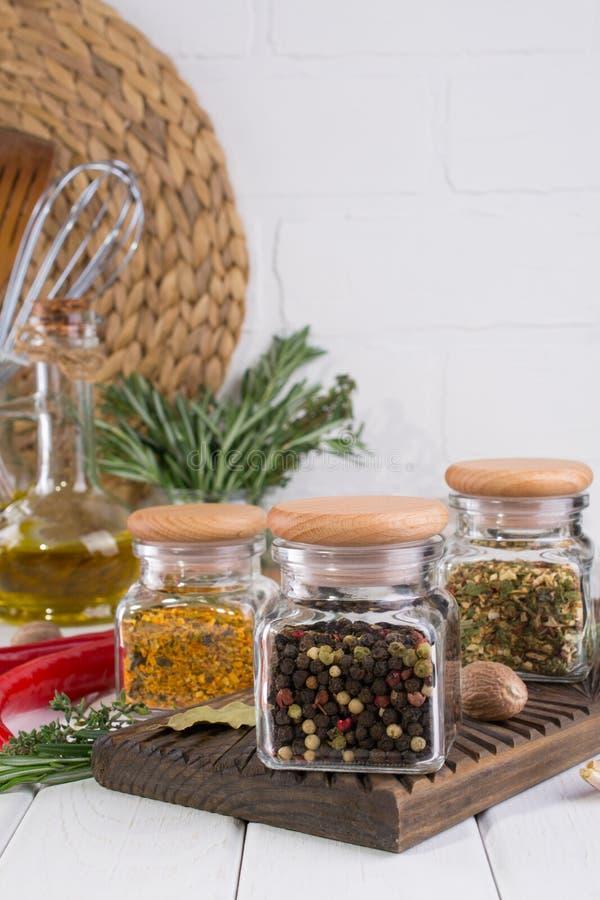Laga mat tabellen med kryddor i exponeringsglaskrus och örter arkivbild