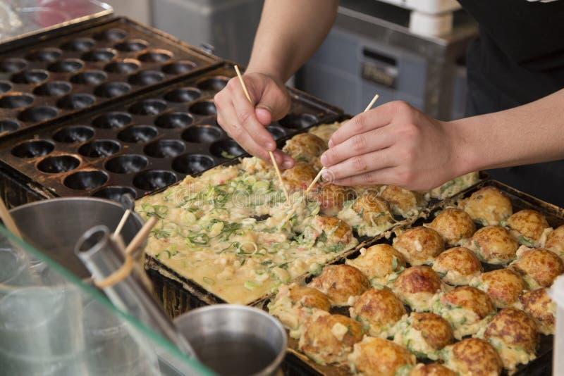 Laga mat Takoyakis på en gataställning i Osaka royaltyfri fotografi
