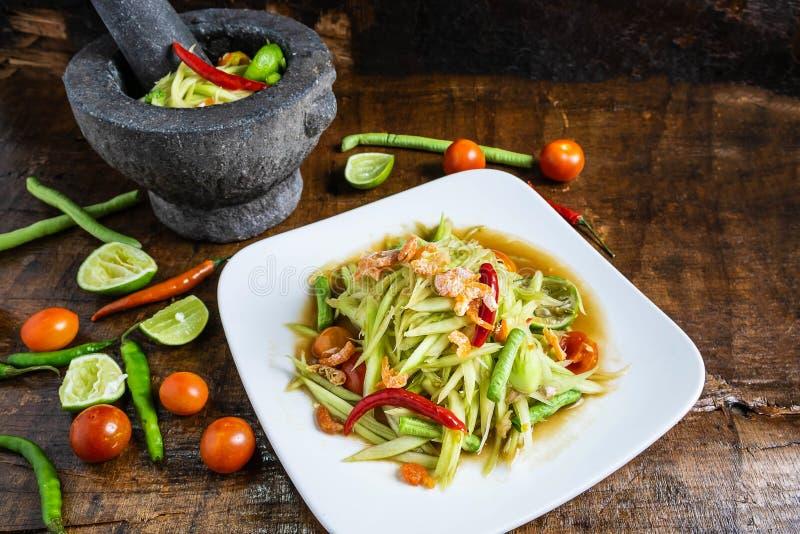Laga mat thail?ndsk mat, papayasallad och papayasallad i en matr?tt med en portion p? en tr?tabell royaltyfria foton