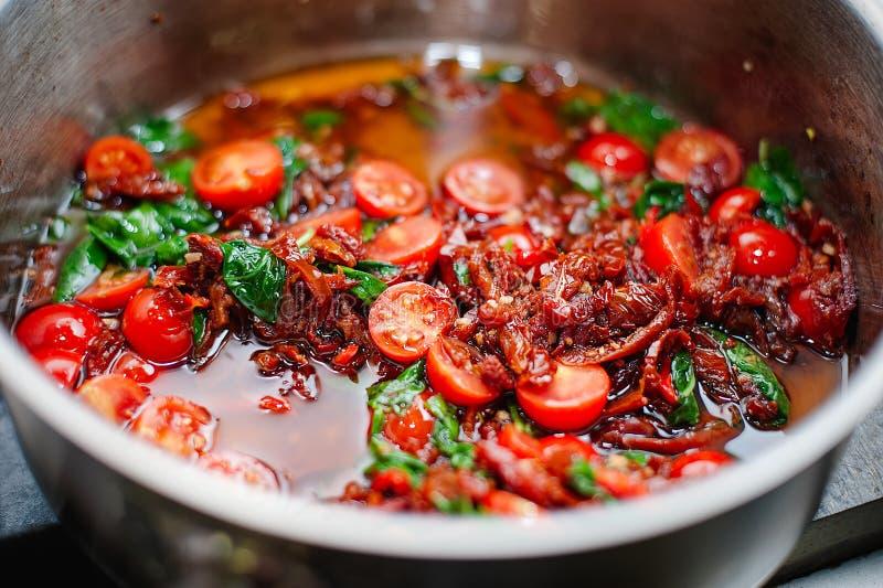 Laga mat tomatsås med tomaten och basilika av kocken arkivfoton