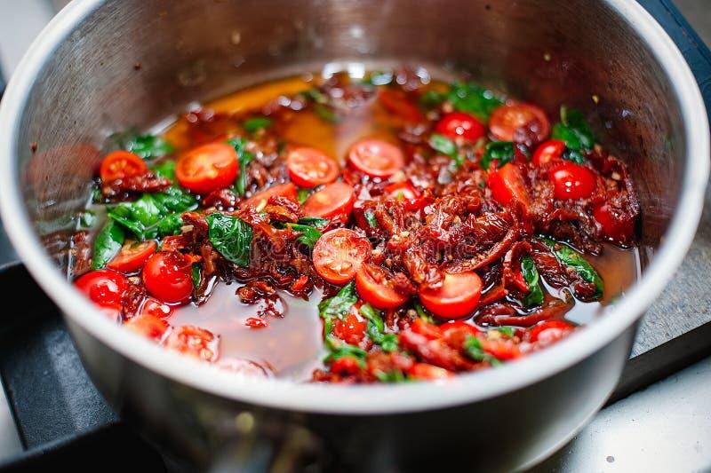 Laga mat tomatsås med tomaten och basilika av kocken royaltyfri bild