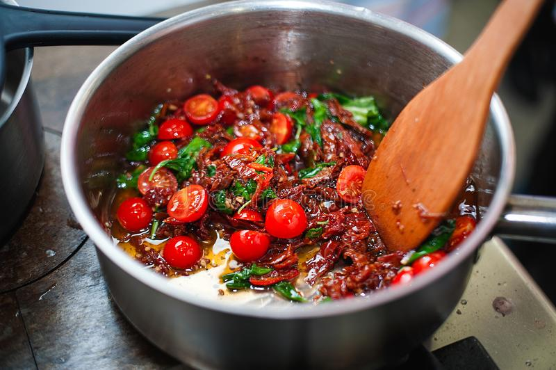 Laga mat tomatsås med tomaten och basilika av kocken royaltyfri foto