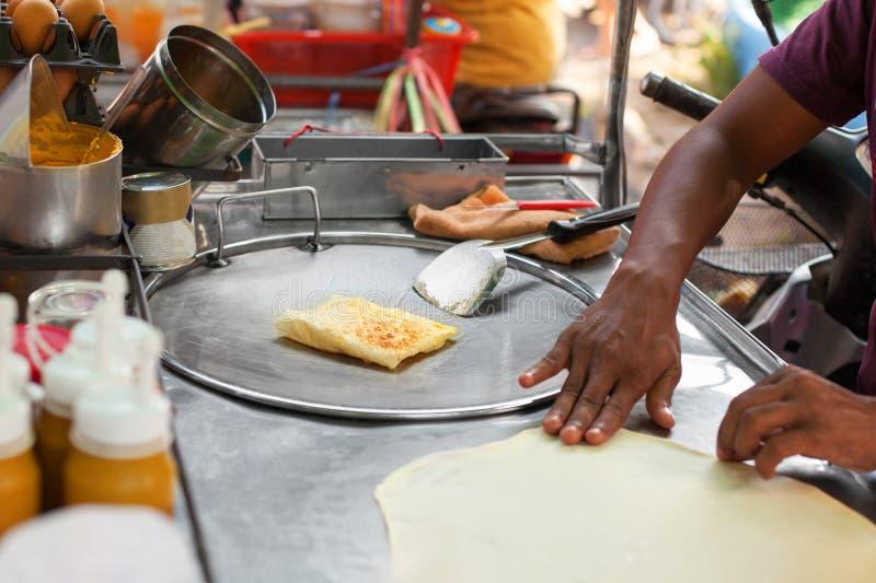 Laga mat traditionella thailändska stekte rotibananpannkakor stäng sig upp, den asiatiska gatamatförberedelsen i Thailand royaltyfri fotografi