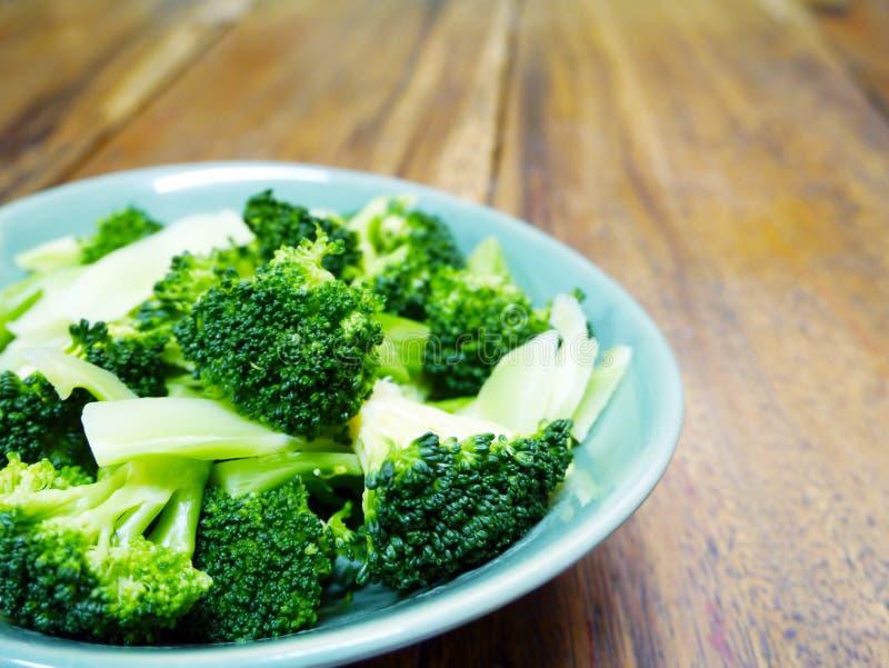 Lagad mat böldbroccoli i grön bunke på trätabellbakgrund royaltyfri fotografi