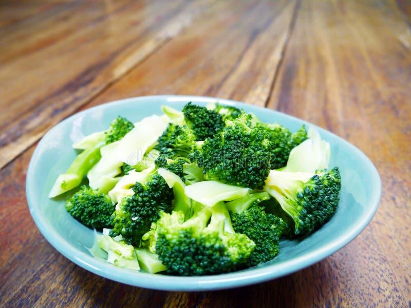 Lagad mat böldbroccoli i grön bunke på trätabellbakgrund arkivbild