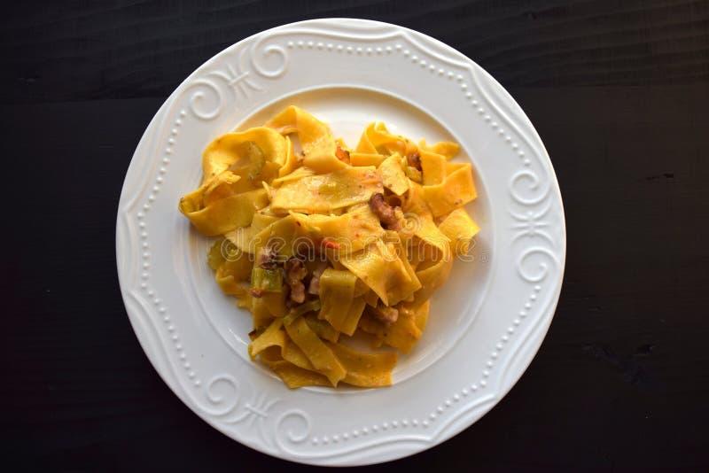 Lagad mat hemlagad tagliatellepasta, grated pecorino och bacon, ost på den vita plattan på gammal träbakgrund arkivbild