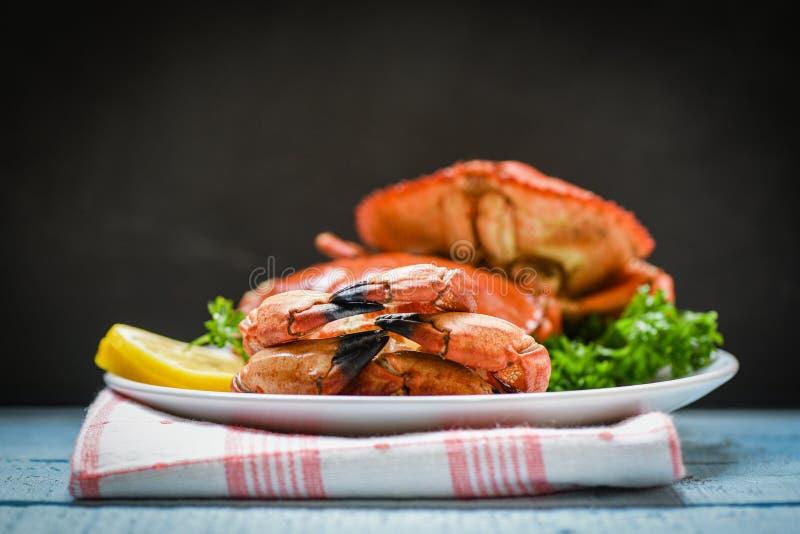 Lagad mat krabba på plattan med citronörter och kryddor på den mörka bakgrunden - skaldjur kokade röd sallad för stenkrabbor royaltyfri foto