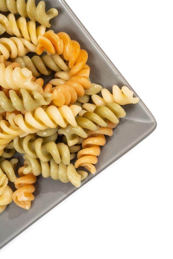 Lagad mat och tjänad som färgrik pasta på den gråa plattan arkivfoton