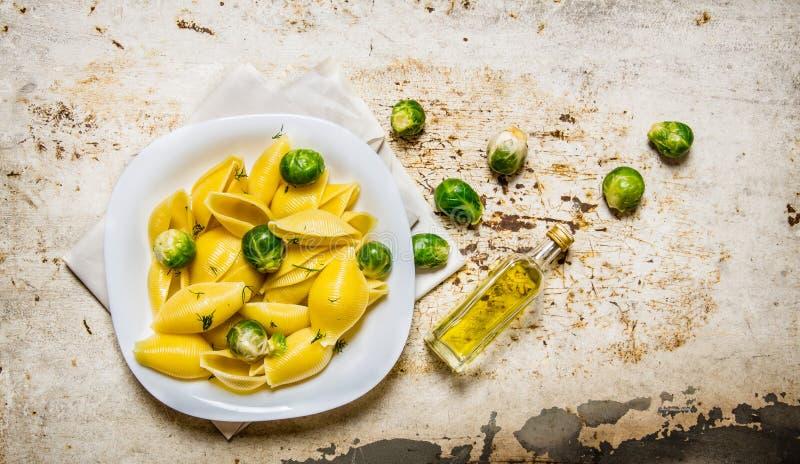 Lagad mat pasta med Bryssel groddar i en vit platta med olivolja royaltyfri fotografi