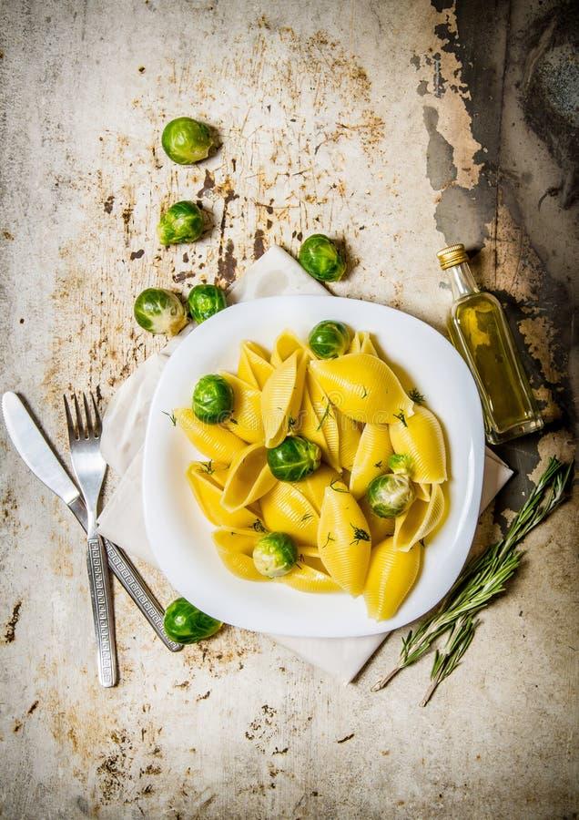 Lagad mat pasta med Bryssel groddar i en vit platta med olivolja royaltyfri foto