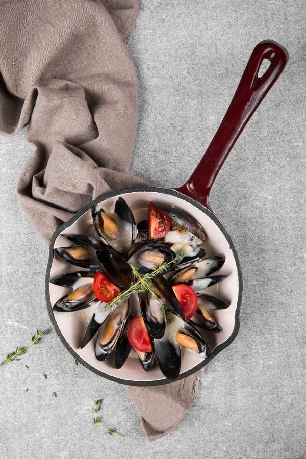 Lagade mat musslor i en panna tjänade som på en servett som garnerades med tomater och timjan Ångade musslor i sås för vitt vin royaltyfri fotografi