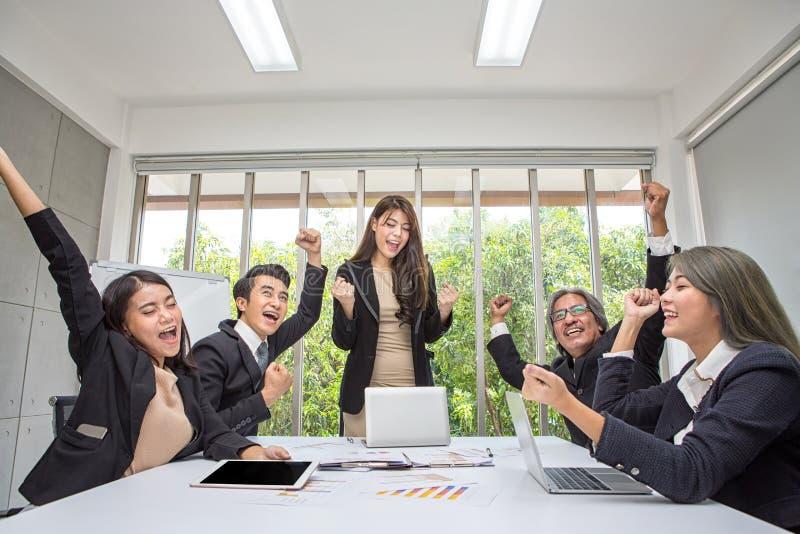 Lagarbete av lyckligt affärsfolk som i regeringsställning hurrar fira framg?ng Aff?rslaget firar ett bra jobb i kontoret asiat arkivbild