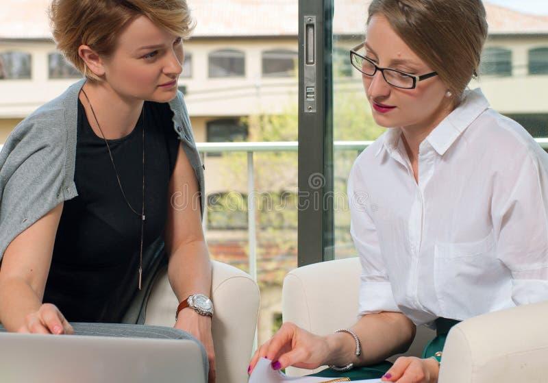 Lagarbetsprocess Två kvinnor med bärbara datorn i regeringsställning royaltyfria foton