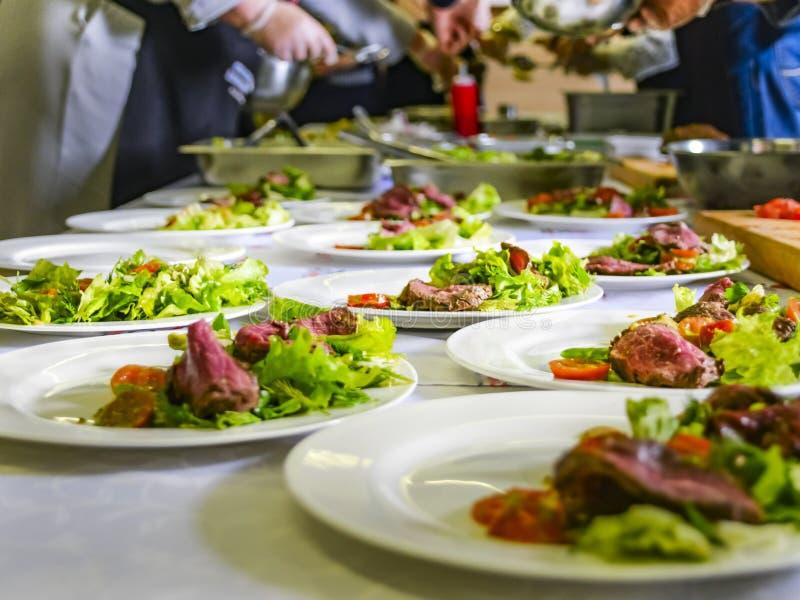 Lagat mat steknötkött, ny sallad och tomater som tjänas som på vita plattor Laga mat mästarklass, seminarium med folk som lär hur fotografering för bildbyråer