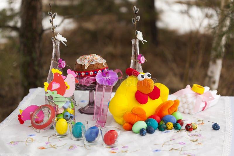 Lagd tabell för påsk: leksakhöna med färgrika påskägg - slösa, göra grön, gulna, rött - påskkaka, pappers- statyetter av hönor royaltyfri bild