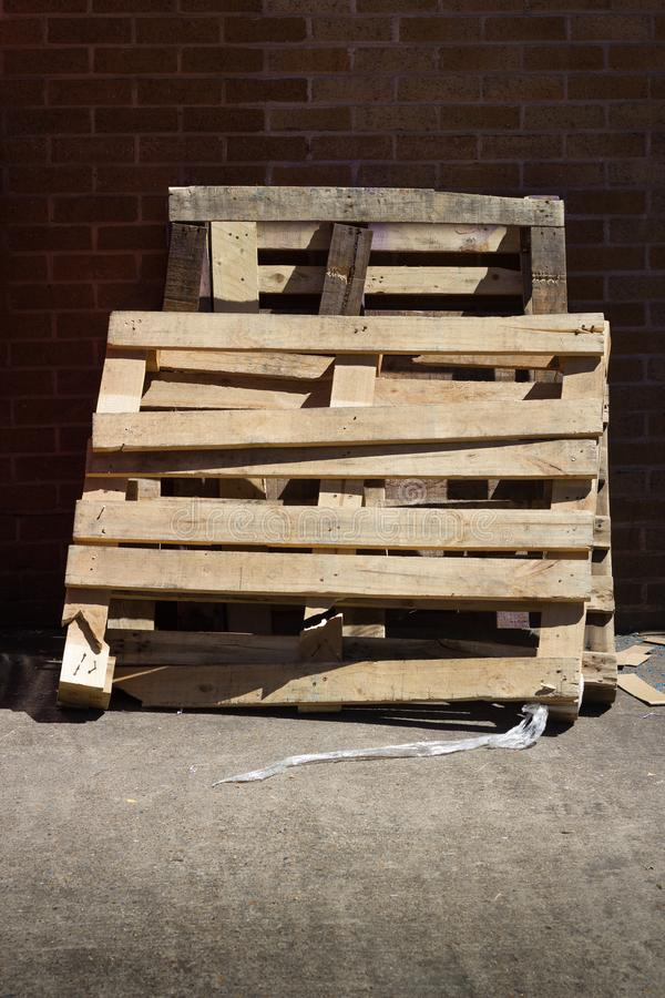 Large Broken Timber Pallets Leaning Against Brick Wall. Cropped in centred object with horizontal slats and empty concrete at bottom of image royalty free stock images