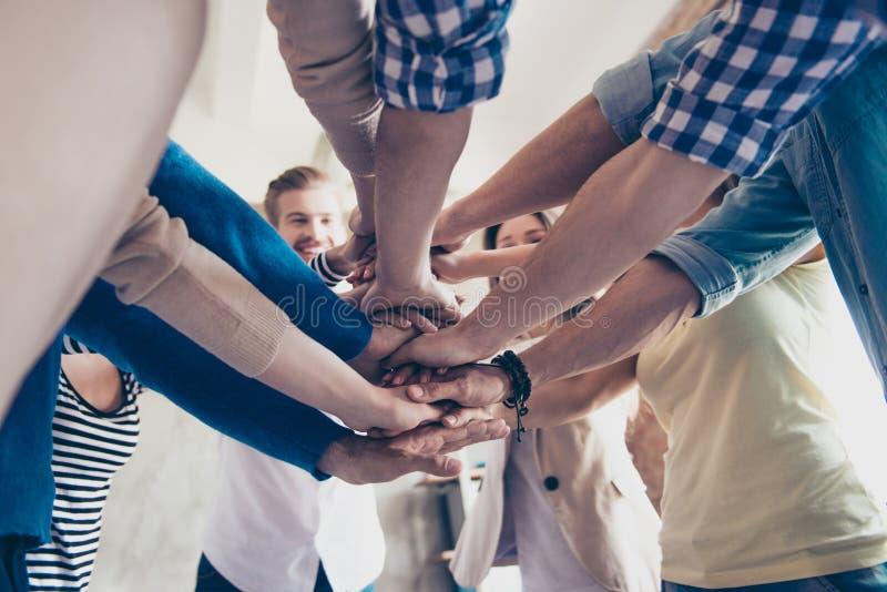 Lage hoek bebouwde mening van collega's die hun handen op bovenkant zetten royalty-vrije stock foto