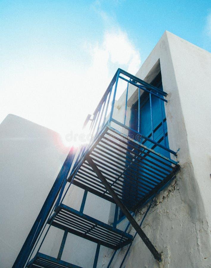Lage hoek die van blauwe trede wordt geschoten die aan een blauwe deur met de zon leiden die in de blauwe hemel glanzen stock foto
