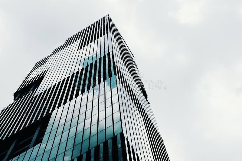 Lage hoek die van een lang high-rise modern bedrijfsgebouw met een duidelijke hemel op de achtergrond wordt geschoten stock afbeeldingen