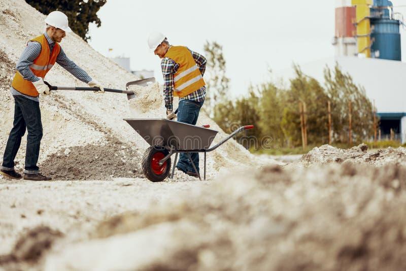 Lage hoek op arbeiders in weerspiegelende vesten met schoppen en kruiwagen stock afbeeldingen