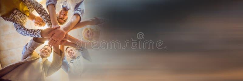 Lage hoek van creatief team die handen en onscherpe zonsondergangovergang samenbrengen stock foto