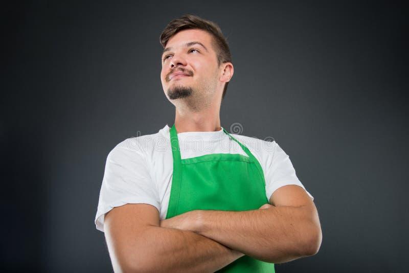Lage hoek van mannelijke supermarktwerkgever met gekruiste wapens stock foto's
