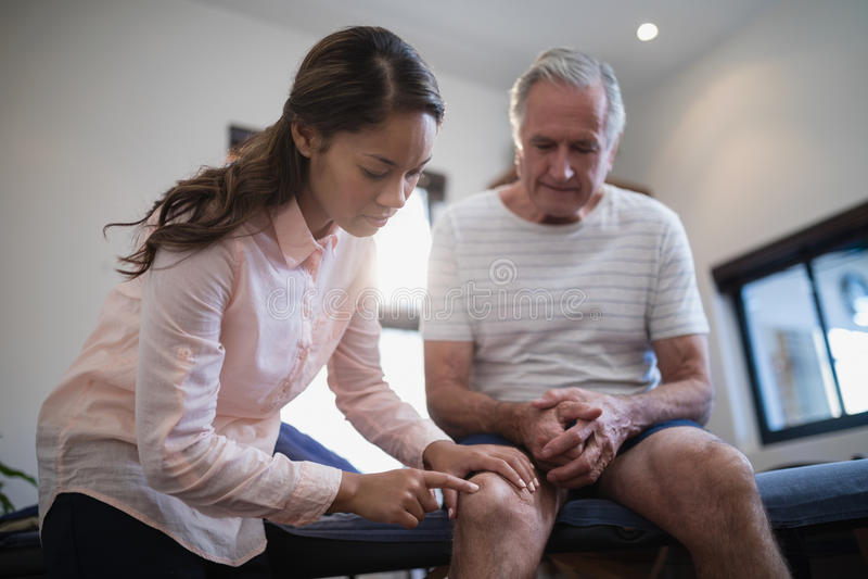 Lage hoekmening die van vrouwelijke therapeut knie onderzoeken terwijl mannelijke geduldige zitting op bed stock afbeeldingen