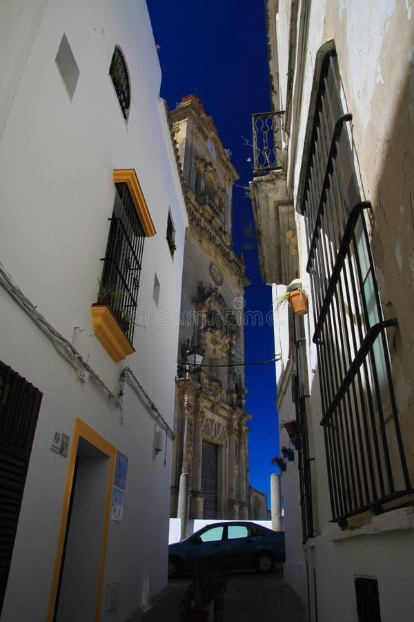 Lage hoekmening over smalle lege steeg met voorgevels van witte huizen en stappen die boven met donkerblauwe hemel in traditionee stock foto's