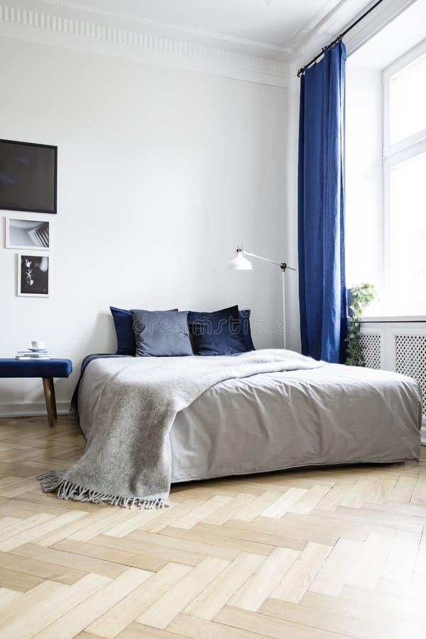 Lage hoekmening van een comfortabel tweepersoonsbed in een hoek van een helder slaapkamerbinnenland met marineblauwe textiel en p stock fotografie