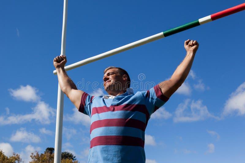 Lage hoekmening van glimlachende die rugbyspeler met wapens tegen blauwe hemel wordt opgeheven royalty-vrije stock fotografie