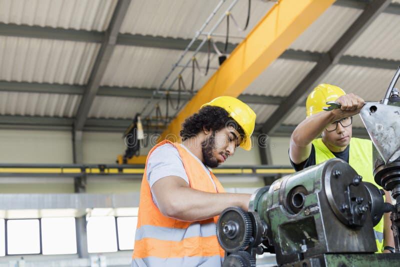 Lage hoekmening van handarbeiders die aan machines in de metaalindustrie werken royalty-vrije stock foto's