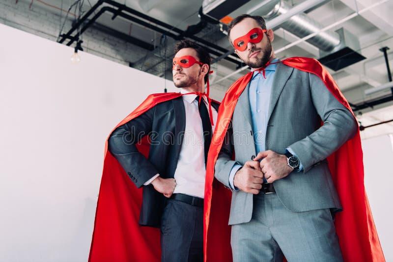 lage hoekmening van knappe super zakenlieden in rode maskers en kaap stock foto's