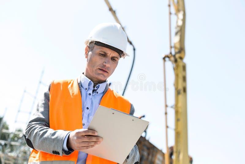 Lage hoekmening van supervisor het schrijven op klembord bij bouwwerf stock foto