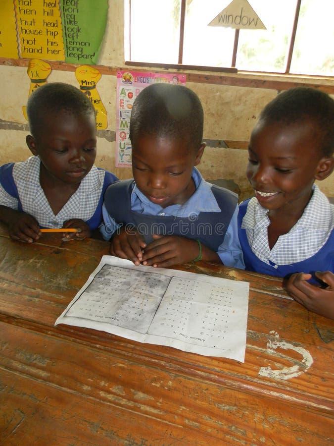 Lage schoolkinderen die Engelse lezing uitoefenen stock afbeelding