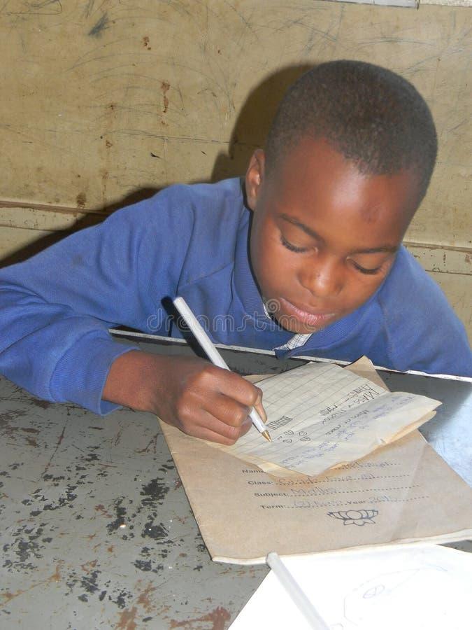 Lage schoolleerling die op school schrijven royalty-vrije stock afbeeldingen